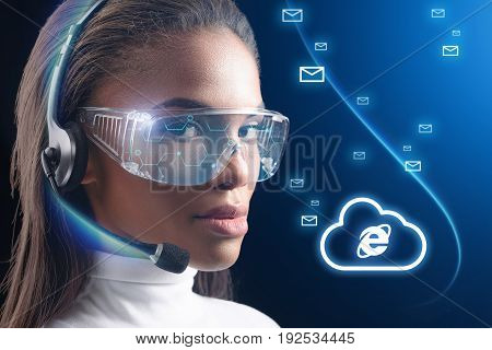 Confident young female operator is sending messages through internet cloud of the future. She is wearing special headset and eyewear