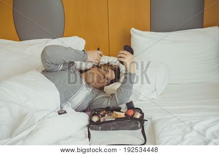 Woman Applying Makeup While She Is Lying On Her Bed