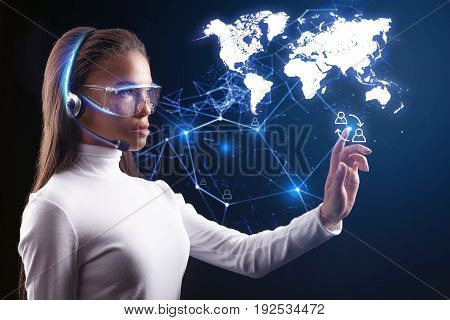 Creating human communication. Serious futuristic female operator is connecting people around the world by internet system. She is wearing headphones and eyeglasses