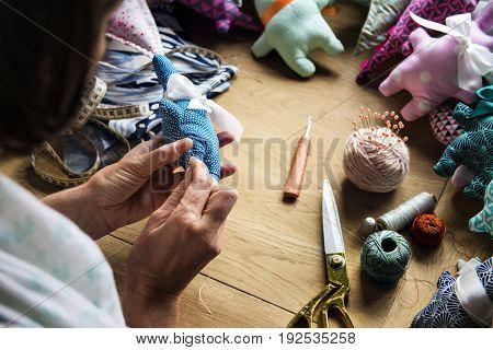 Closeup of hands sewing doll handicraft handmade