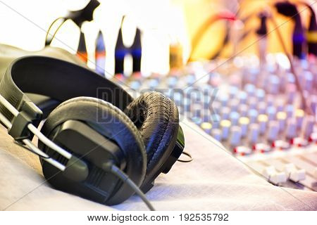 Headphones and a remote control of sound in the background with a shallow depth of field