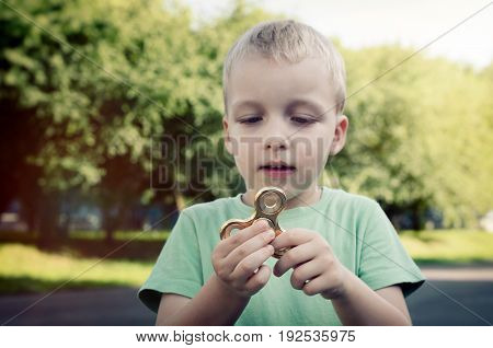 Little boy with a fidget spinner outdoors. spinner fidget child stress adhd attention fad boy concept