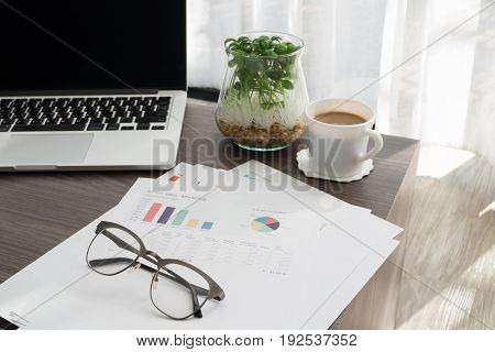 wood office table with business summary report white coffee cup and blank screen on laptop at office place.