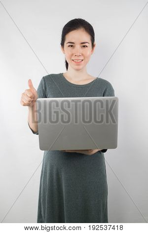 young woman be pregnant in maternity clothes hold laptop on gray cement wall background. concept of excellence sign.