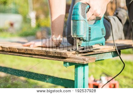 Photo of worker with electric jigsaw in park