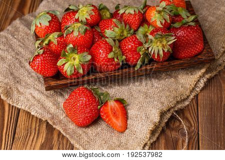 Picture of fresh ripe strawberry on wooden plate, canvas fabric close-up