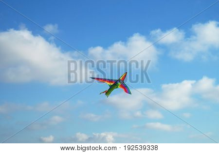 Kite flying in the shape of a multi-colored airplane against the sky
