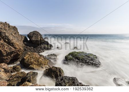 Pacific coast rocks and waves with motion blur at Point Dume in Malibu, California.