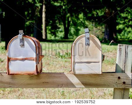 Two rural style mailboxes on a wooden stand