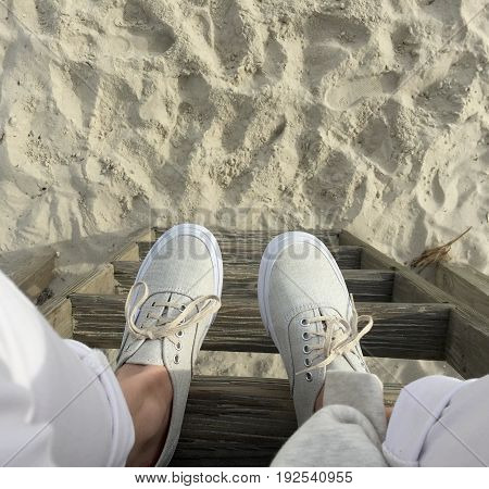 white jeans and beige sneakers, on a ladder on the beach
