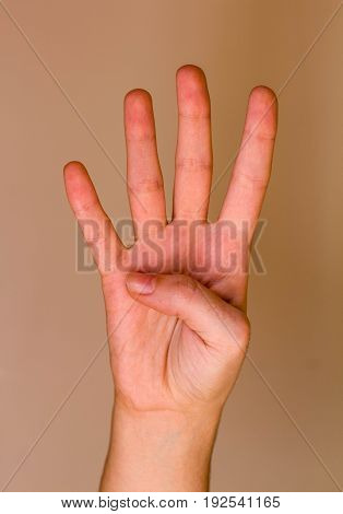 Right hand of a young woman doing her fingers the number four
