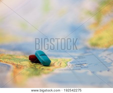 Two small pills on a global geopolitical map