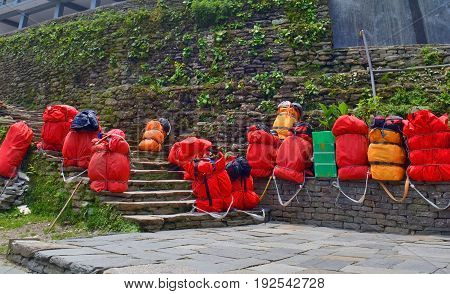 Huge red backpacks for mountain expedition on stairs. Porter Mountaineering equipment. Nepal, Annapurna Base Camp track.