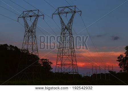 Power Transmission Tower Silhouetted Against Sunset Glow