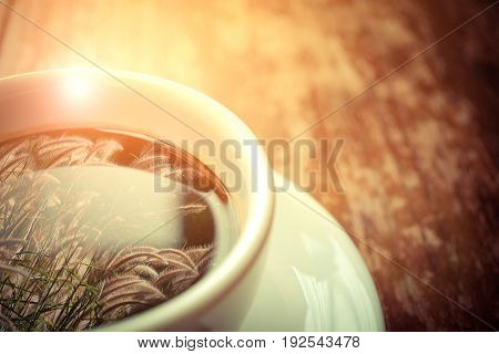 Grass flower (poaceae) reflection on Coffee in white cup on wood table process in vintage style