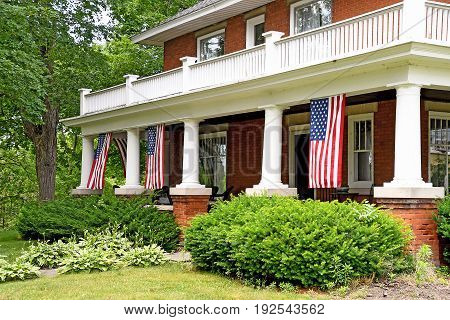 American flags decorating house front porch with white pillars