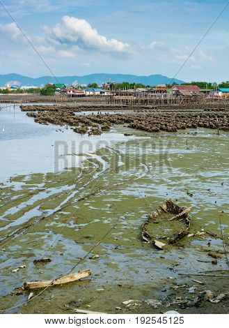 Abandoned wooden boat submerged in muddy at low tide