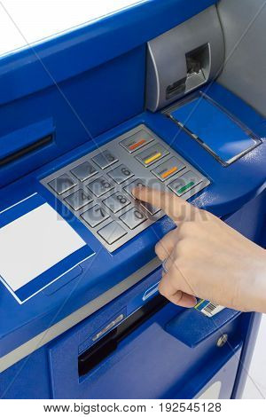 Hand of a woman using an ATM. Woman using an atm machine pressing her password.