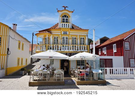 Costa Nova Portugal - June 09 2017: Famous resort on the Atlantic coast in Beira Litoral Portugal. Popular tourist destination to spend vacation time. Tourists has a dinner in restaurant
