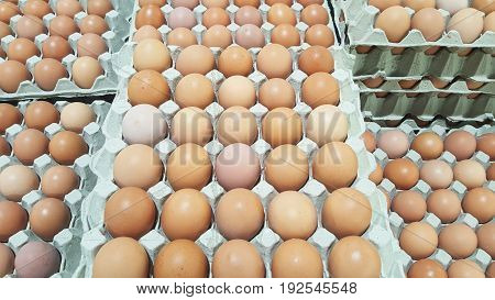 background of fresh brown eggs on paper tray for sale at a floating market