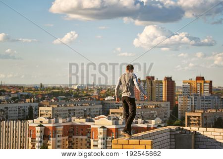 A lone roofer walks along the edge of the roof fence on a high-rise building. Courage and adrenaline.
