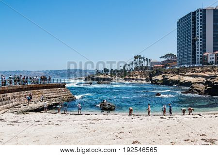 LA JOLLA, CALIFORNIA - JUNE 16, 2017:  Visitors on the sea wall and beach of the Children's Pool, with surrounding hotels and natural sandstone rock formations.