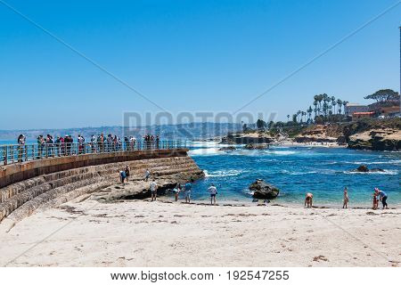 LA JOLLA, CALIFORNIA - JUNE 16, 2017:  Visitors on the beach and on the sea wall of the Children's Pool, a popular location for viewing wildlife and beachcombing.