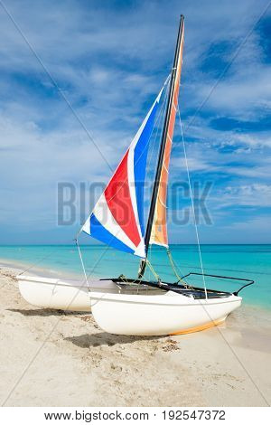 The tropical Varadero beach in Cuba with a colorful catamaran sailboat