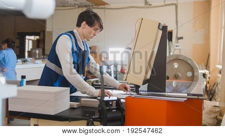 Press operator works in a typographical machine, in a printing factory