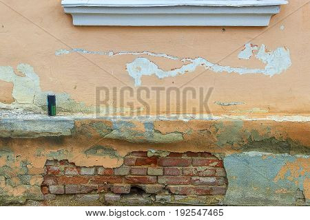 Part of a wall of the old brick house with a window sill and eaves above the base on which there is a metal tin from under drinks.