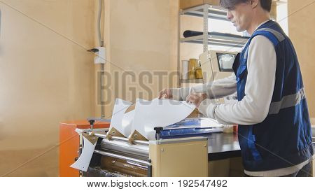 The operator of the printing house during work, in a printing factory