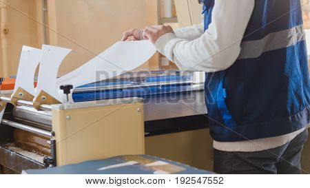 The typography worker pulls the paper from the machine, in a printing factory