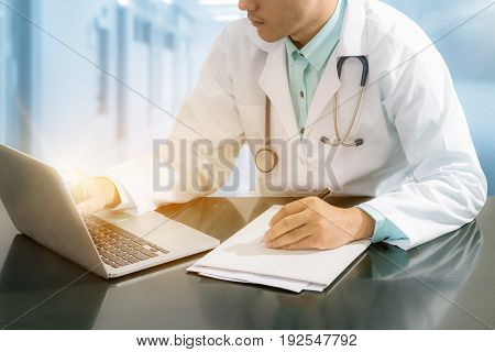 Doctor Working On Desk With Laptop