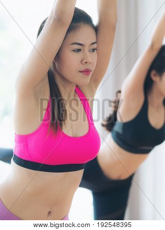 Women Exercising Yoga Pose In Fitness Gym Class