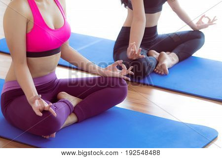 Women Doing Yoga Lotus Pose In Fitness Gym Class