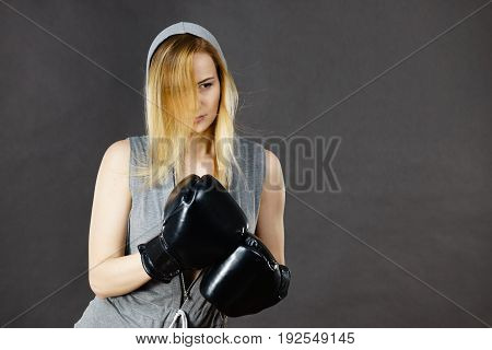 Young hooded woman fighting boxing. Blonde attractive girl wearing black punch gloves. Sport and fitness power exercising on grey