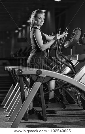 Young woman at the gym exercising. Run on on a machine. Jogging workout in dark fitness club. Cardio. Black and white.