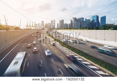 Busy road and city background during rush hour with motion-blurred vehicle car in Singapore city highway. Modern buildings office in background. Modern city transportation background concept.