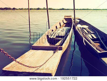 Two old wooden boats are close docked to river side Vintage color filter style