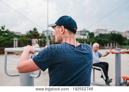 A man trains on sporting equipment in a city in the open air. The concept of a healthy lifestyle and accessibility of sports training for every person. Available sports equipment. Street sports.