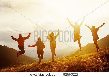 Group of five happy friends is running and jumping in sunset light on background of mountains. Happiness and friendship concept