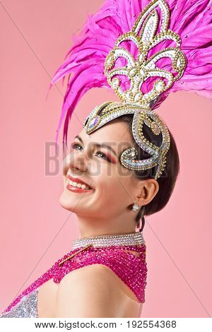 Beautiful woman in carnival costume with pink feathers and rhinestones.Beautiful professional make-up perfect headdress with natural feathers . Pink background .