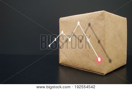 On a dark background a box. It shows the graph going down. Business graph falls.