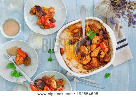 Party dinner table concept. Baked chicken breast with vegetables on blue wooden table with wine top view
