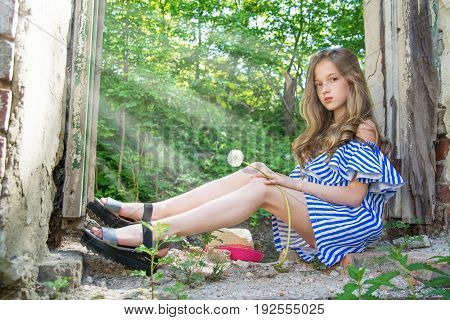 a young girl is sitting in the window opening, in the devastated building in the Park, portrait of a young beauties