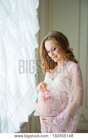Pregnant woman holding pink baby shoes on her belly.