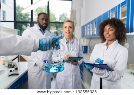 Scientist Holding Flask With Group Of Students Taking Notes Making Research In Laboratory, Mix Race Team Of Doctors Writing Results Of Experiment In Lab