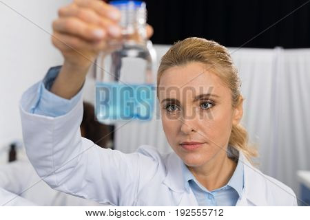 Female Scientist Examine Flask With Blue Luquid Working In Modern Laboratory, Attractive Woman Researcher Making Experiment In Lab