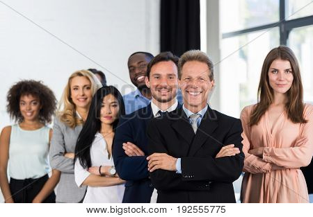 Boss With Group Of Businesspeople In Creative Office, Mature Successful Businessman Leading Business People Team Stand Folded Hands, Professional Staff Happy Smiling