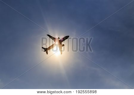 Silhouette airplane taking off over blue sky at sun background.